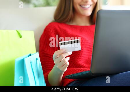 Nahaufnahme von einem Mädchen Hand halten Sie eine Kreditkarte und Kauf auf Linie mit einem Laptop und Einkaufstaschen - Stockfoto