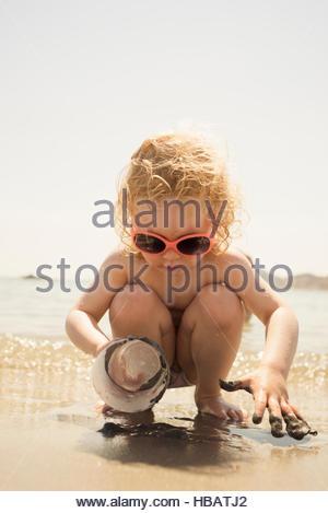 Niedliche Mädchen hocken am Strand spielen mit Plastikbecher in Sand, Alicante, Spanien - Stockfoto