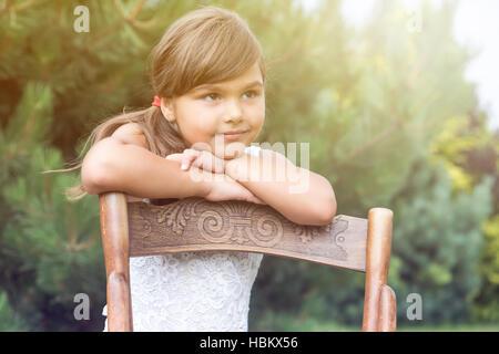 Porträt der langhaarige Brünette Mädchen stützte sich auf einen Jahrgang Holzstuhl. Das Sonnenlicht ist in der oberen - Stockfoto