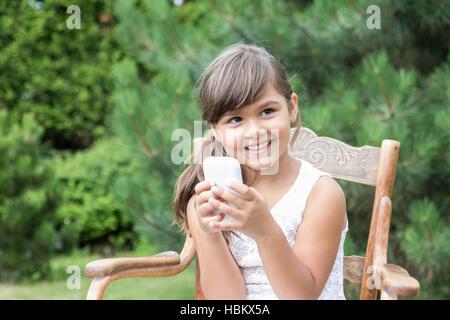 Lächelndes langhaarige Brünette Mädchen sitzt auf und alten Holzstuhl im Freien. Kleines Mädchen hält eine Smartphone - Stockfoto