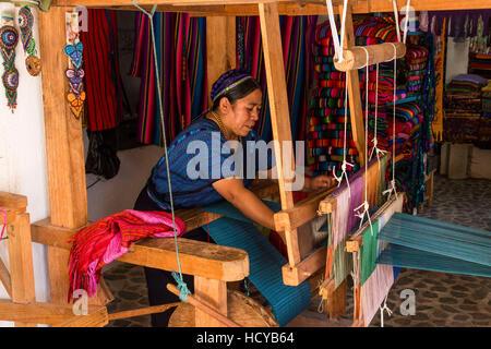 Eine Maya-Frau, trägt typische Tracht webt Stoff auf einem Fuß betätigt Webstuhl in Werkstatt in San Antonio Palopó, - Stockfoto