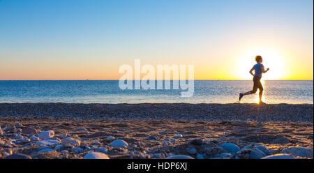 Silhouette der Sportlerin am Ocean Beach bei Sonnenaufgang - Stockfoto