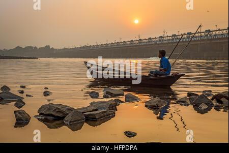 Ein Ruderer sitzt auf seinem Boot bei Sonnenuntergang am Fluss Damodar nahe Durgapur Barrage, West Bengal, Indien. - Stockfoto