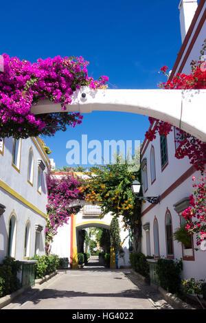 Eine typische Straße in Puerto De Mogan mit Wand-Blumen, die violetten Bougainvillea um die Bögen enthält. - Stockfoto