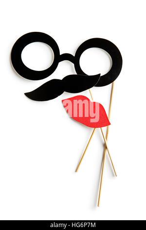 Fake-Lippen, Gläser und Schnurrbärte auf Stöcken. Isoliert auf weißem Hintergrund. - Stockfoto