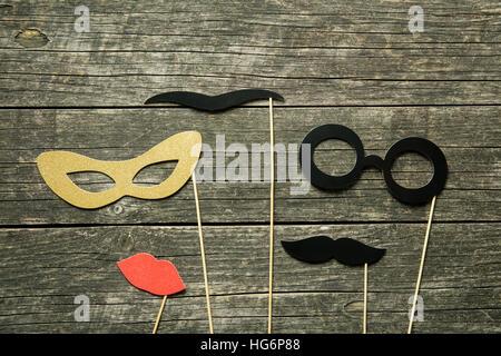 Fake-Lippen, Gläser und Schnurrbärte auf Stöcken auf alten hölzernen Hintergrund. - Stockfoto