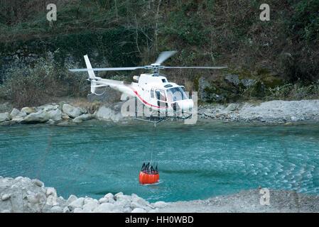Helikopter-sammeln Wasser in einem Eimer von einem Bergfluss zur Brandbekämpfung und pendeln die Flammen, Nahaufnahme - Stockfoto