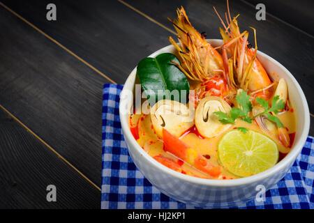 Closeup Tom Yum Soup oder Fluss Garnelen scharf saure Suppe (Tom Yum Goong) auf Holztisch mit blauen Tischdecke, - Stockfoto