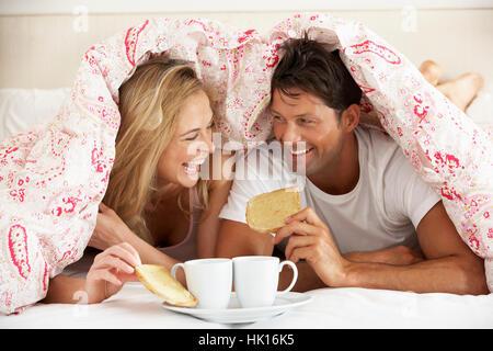 Paar kuschelte sich unter die Bettdecke zu frühstücken - Stockfoto