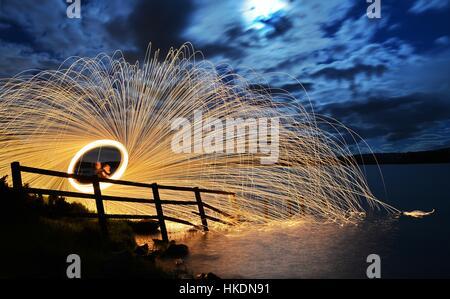 Eine Langzeitbelichtung von Stahlwolle Spinnen auf einem mit Funken spiegelt sich in einem See - Stockfoto