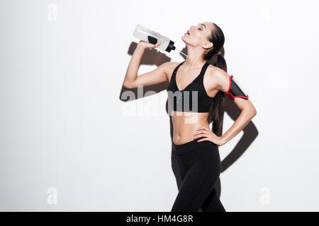 Verführerische junge Sportlerin gießt Wasser aus der Flasche auf sich selbst auf weißem Hintergrund - Stockfoto