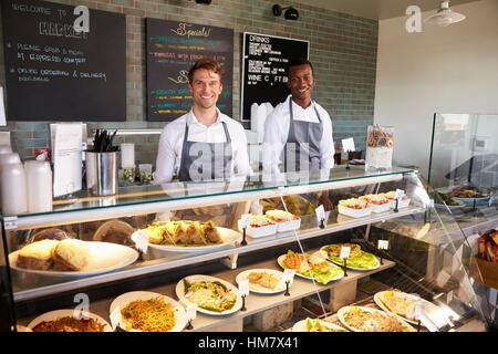 Männliche Mitarbeiter hinter der Theke In Feinkost - Stockfoto