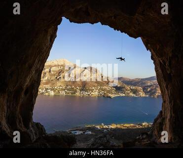 Junger Mann Klettern auf Felsen - Stockfoto