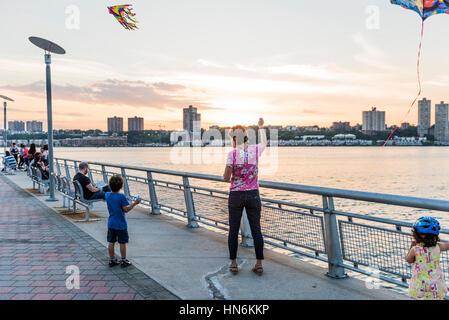 New York, USA – 18. Juni 2016: Frau und Kinder fliegen Drachen am Pier 1 in Riverside Park während des Sonnenuntergangs - Stockfoto