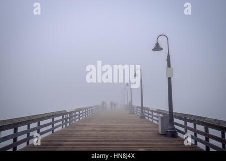 Silhouetten von Menschen im Nebel auf dem Imperial Beach Pier. - Stockfoto