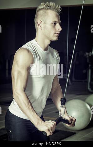 Hübscher Jüngling Training Trizeps auf Fitnessgeräte, Hebel an Kabeln - Stockfoto