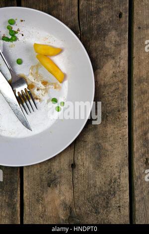 Draufsicht der Reste auf einem Teller mit Messer und Gabel auf einem rustikalen hölzernen Hintergrund - Stockfoto