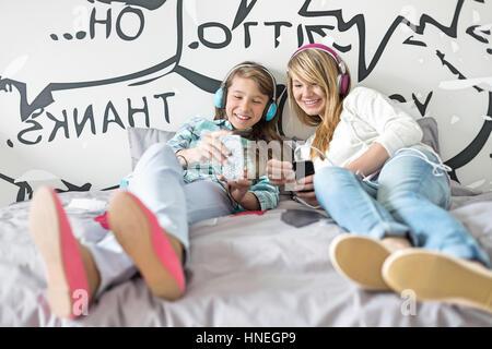 Entspannte Schwestern Musikhören zu Hause - Stockfoto