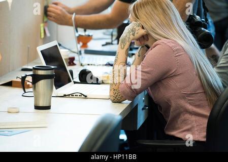 Frau, die Konzentration auf die Arbeit im gemeinsamen Büroraum - Stockfoto