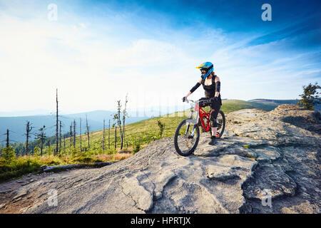 Weibliche MTB Mountainbiker genießt die Aussicht während der sonnigen Tag in Bergen - Stockfoto