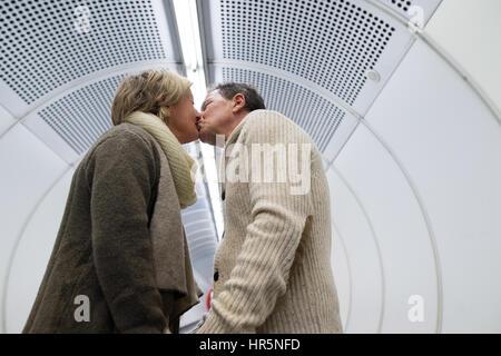 Schönes älteres paar zu Fuß auf dem Flur der u-Bahn in Wien ziehen eine Trolley-Gepäck, küssen. - Stockfoto