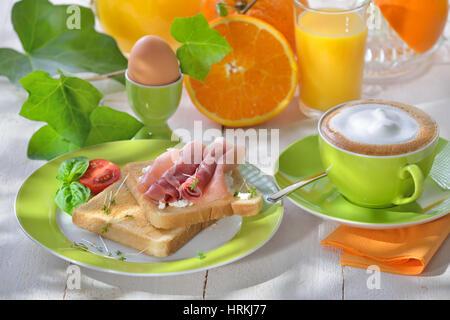 Frühstück mit Schinken-Toast, ein gekochtes Ei, Orangensaft und eine Tasse cappuccino - Stockfoto