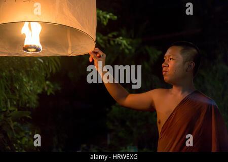 Buddhistischer Mönch hält eine traditionelle schwimmende Laterne mit einer Kerze in der Nacht. Nacht Feier in einem - Stockfoto