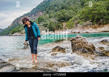 attraktive Mode Model Mädchen stehen auf dem nassen Felsen barfuß, Abhaltung Bergschuhe - Stockfoto