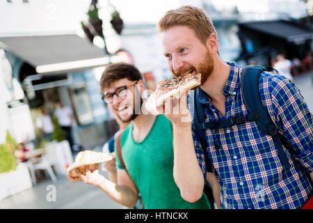 Positiven glücklich Studenten Essen Pizza auf Straße - Stockfoto
