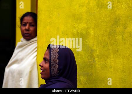 Eine indische Frau vor einer gelben Wand, Khajuraho, Indien - Stockfoto