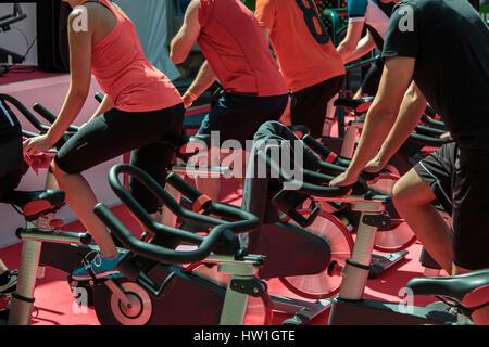Gruppe von jungen und Mädchen in der Turnhalle: Workout mit Spinning-Bikes - Stockfoto