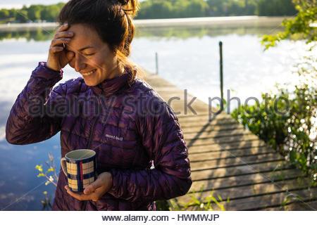 Eine junge Dame wischt Schlaf aus den Augen halten Sie eine Kaffeetasse auf einem See vordere Dock. - Stockfoto