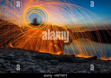 Eine Person steht auf einem Felsen gegen einen See in der Abenddämmerung Spinnerei Stahlwolle auf Feuer mit fliegen - Stockfoto