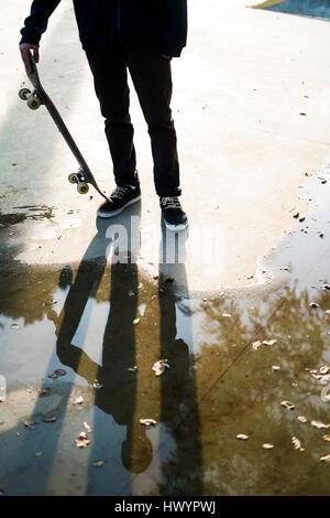 Skateboarder in einem Skatepark spiegelt sich in einer Pfütze - Stockfoto