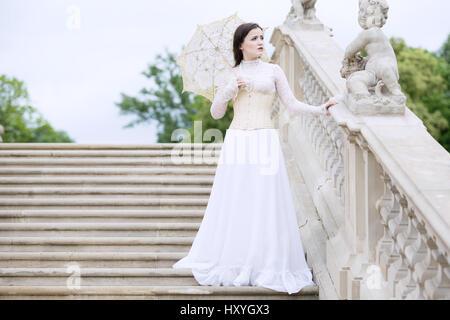 Frau in weißen viktorianischen Kleid mit Regenschirm auf Treppen - Stockfoto