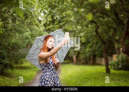 Frau mit Blumen, Tampere, Finnland, Pirkanmaa Kleid stehend mit Schirm in Park und nehmen selfie - Stockfoto