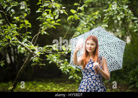 Finnland, Pirkanmaa, Tampere, Frau mit geblümten Kleid mit Regenschirm in Park und unter selfie - Stockfoto
