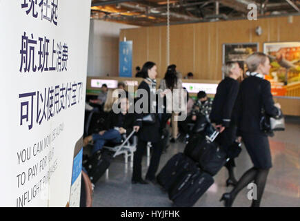 (170405)--Peking, 5. April 2017 (Xinhua)--Finnair Cabin Crew Spaziergang vorbei an einem Banner liest Alipay akzeptabel - Stockfoto