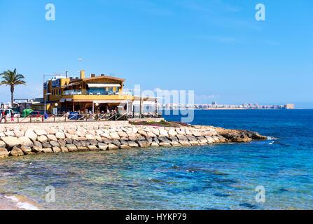 Punta Prima, Spanien - 28. März 2017: Touristen sitzen in einem Café direkt am Meer. Punta Prima ist ein beliebter - Stockfoto