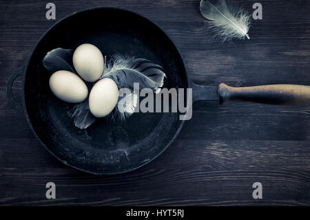 Drei Hühnereier in der Schale liegen in einer gusseisernen Pfanne, Draufsicht, Vintage Muskelaufbau - Stockfoto