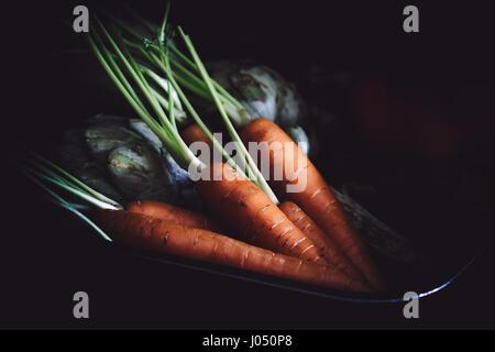 Topf mit Karotten und Artischocken auf schwarzem Hintergrund. - Stockfoto