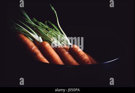 Bündel von Karotten auf schwarzem Hintergrund. Rustikalen Stil. - Stockfoto