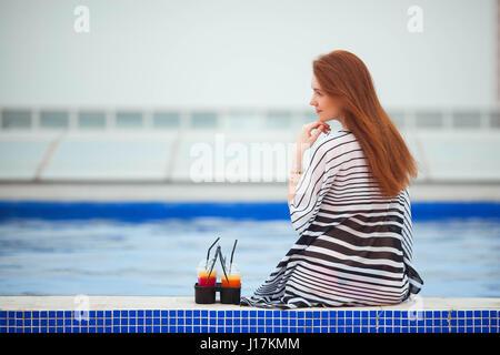 Schönes rothaarige Mädchen in einem gestreiften Pareo sitzt mit dem Rücken zur Kamera am Pool. Als nächstes werden - Stockfoto