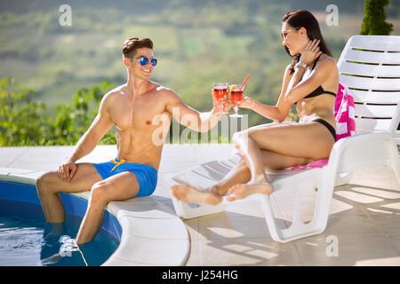 Junges Paar im nächsten Pool Cocktails genießen - Stockfoto