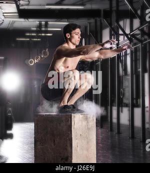 Passen Sie junge Männer-Kiste springen in einem Crossfit Gym. Sportler Datenzugriffsmöglichkeit - Stockfoto