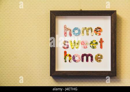 Umrahmt von Buchstaben traute Heim an einer Wand aufgehängt - Stockfoto