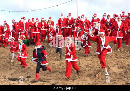 Perranporth, Cornwall, UK. 18. Dezember 2016. Santa auf dem Sand eine jährliche Charity laufen am Strand von Perranporth - Stockfoto