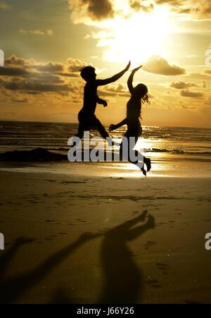 Freunde-High-Five am Strand bei Sonnenuntergang. - Stockfoto