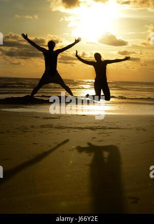 Freunde springen in die Luft am Strand bei Sonnenuntergang. - Stockfoto