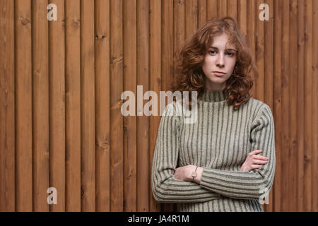 Die Holzwand steht eine schöne rothaarige Mädchen in einen grünen Pullover. Sie kreuzt die Arme und stark in die - Stockfoto